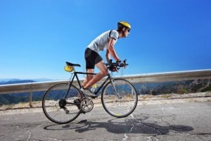 6-25 8038052-a-male-cyclist-riding-a-bike-uphill-along-a-road-clear-summer-day